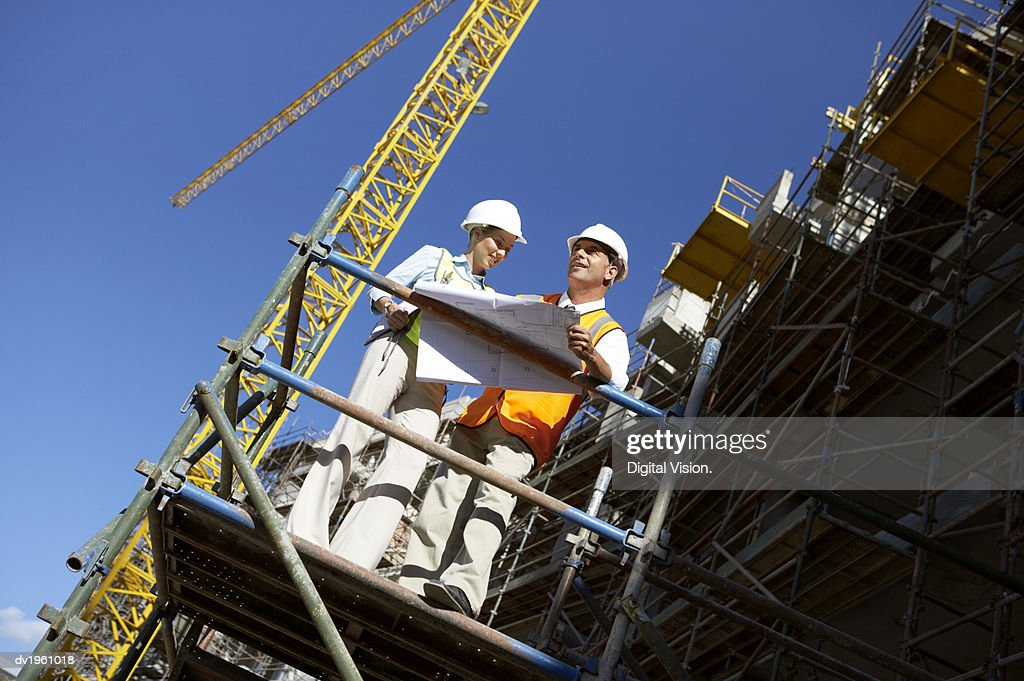 Two Well Dressed Colleagues Standing Side by Side on a Construction Frame, Looking at Blueprints : Stock Photo