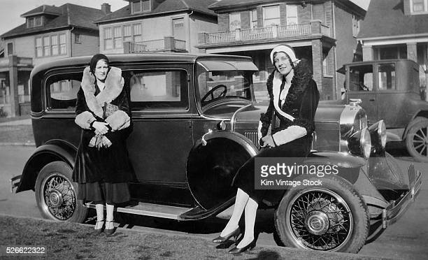 Two well dressed women strike a pose with their 1930 Pontiac automobile on a Detroit neighborhood street in the early 1930s