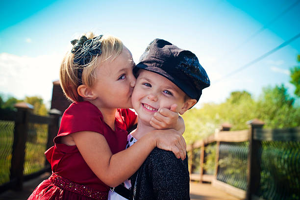 Child Is Kissing A Cat Two Well Dressed Toddlers Embracing And Smiling On Bridge