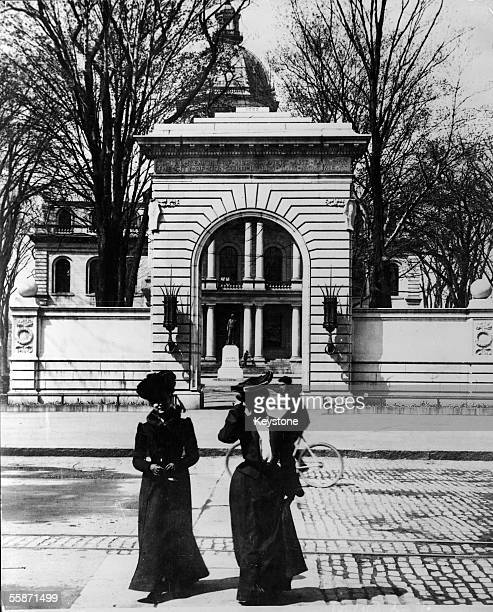 Two welldressed women pose for a picture on the sidewalk across the street from the state capitol building Concord New Hampshire early 1900s A boy...