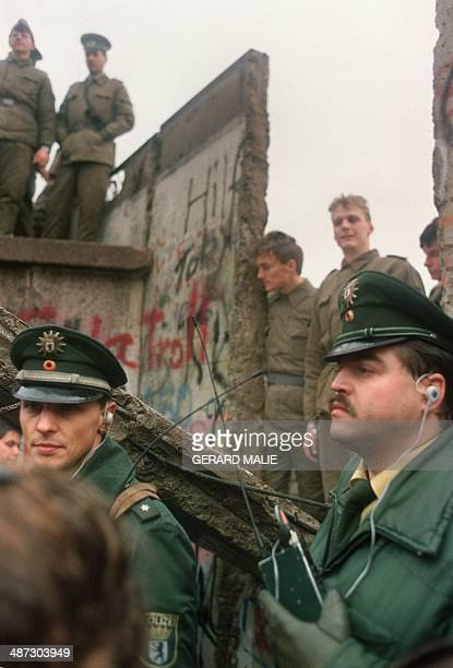 Two West German policemen prevent people from approaching as East German Vopos stand on and near a fallen portion of the Berlin Wall 11 November 1989...