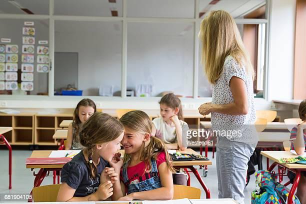 two whispering schoolgirls at class - grundschulzeit stock-fotos und bilder
