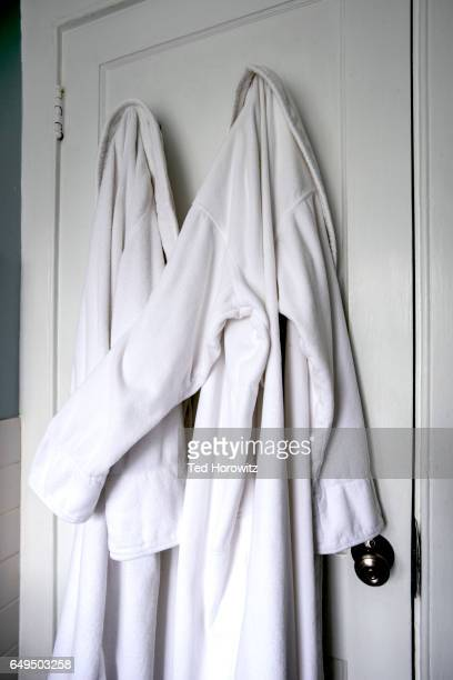two white bathrobes hugging. - romance film stock photos and pictures