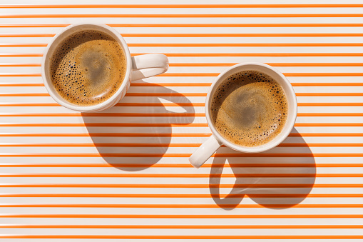 Two white coffee cup on orange striped table top view 1157614908