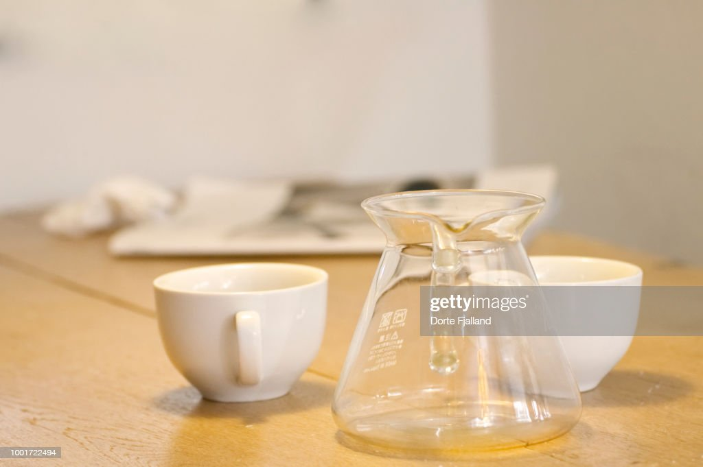 Two white coffee cups and an empty glass coffee pot and a wooden table : Foto de stock