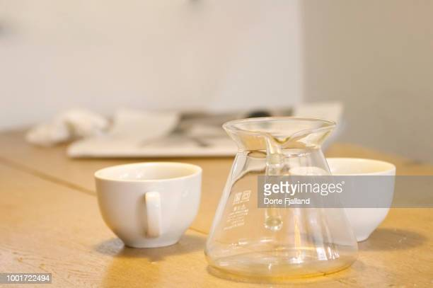 Two white coffee cups and an empty glass coffee pot and a wooden table