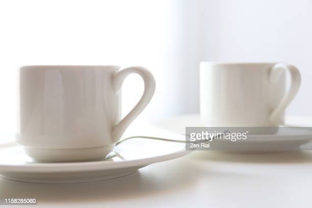 two white coffee cups on saucers against white background - saucer stock pictures, royalty-free photos & images
