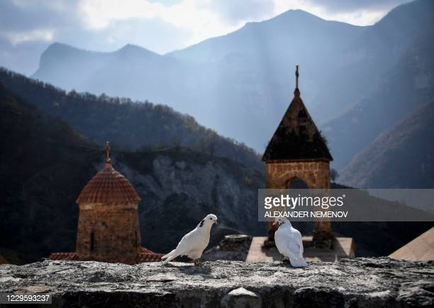 Two white doves stand on a wall of the 12th-13th century Orthodox Dadivank monastery, outside the town of Kalbajar on November 12 during the military...