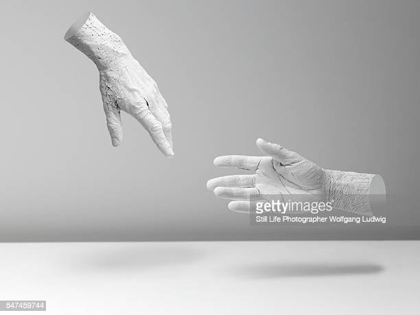 two white hands in an abstract space, one hand tries to reach the other hand for help