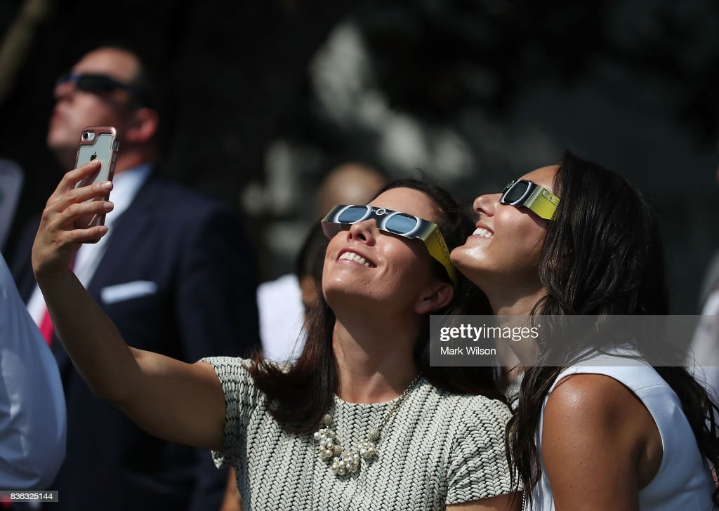 Two White House staff members take a selfie while wearing special glasses to view the solar eclipse, on the South Lawn at the White House on August 21, 2017 in Washington, DC. Millions of people have flocked to areas of the U.S. that are in the 'path of totality' in order to experience a total solar eclipse.