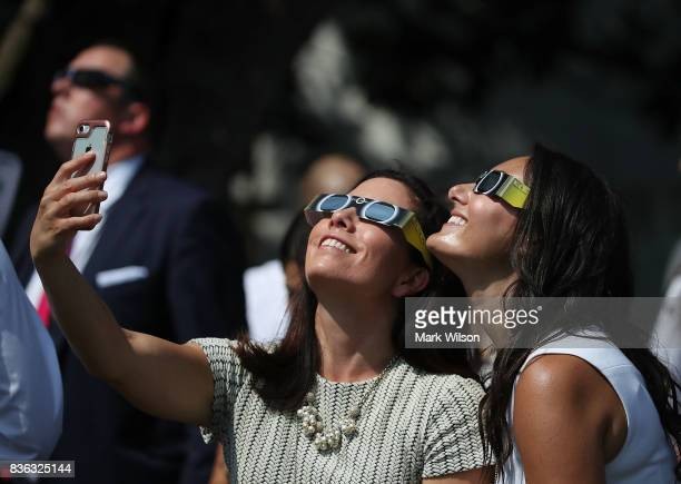 Two White House staff members take a selfie while wearing special glasses to view the solar eclipse, on the South Lawn at the White House on August...