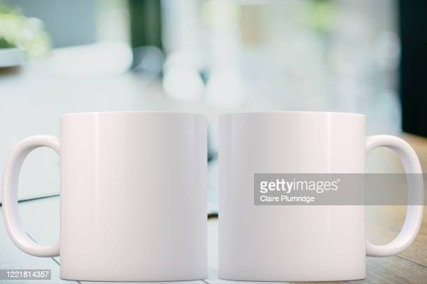 two white mugs mockup on a desk, with a blurred background. perfect for businesses selling mugs, just overlay your quote or design on to the image. - ウェスト・バークシャー ストックフォトと画像