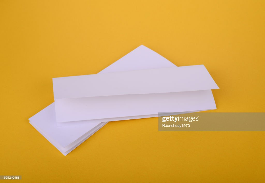 two white paper fourfold brochure mockup on yellow background stock