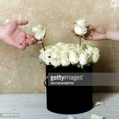 Two White Roses In Round Black Vase And The Hands Of Men And Women