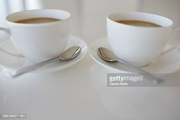 Two white tea cups and spoons, close-up