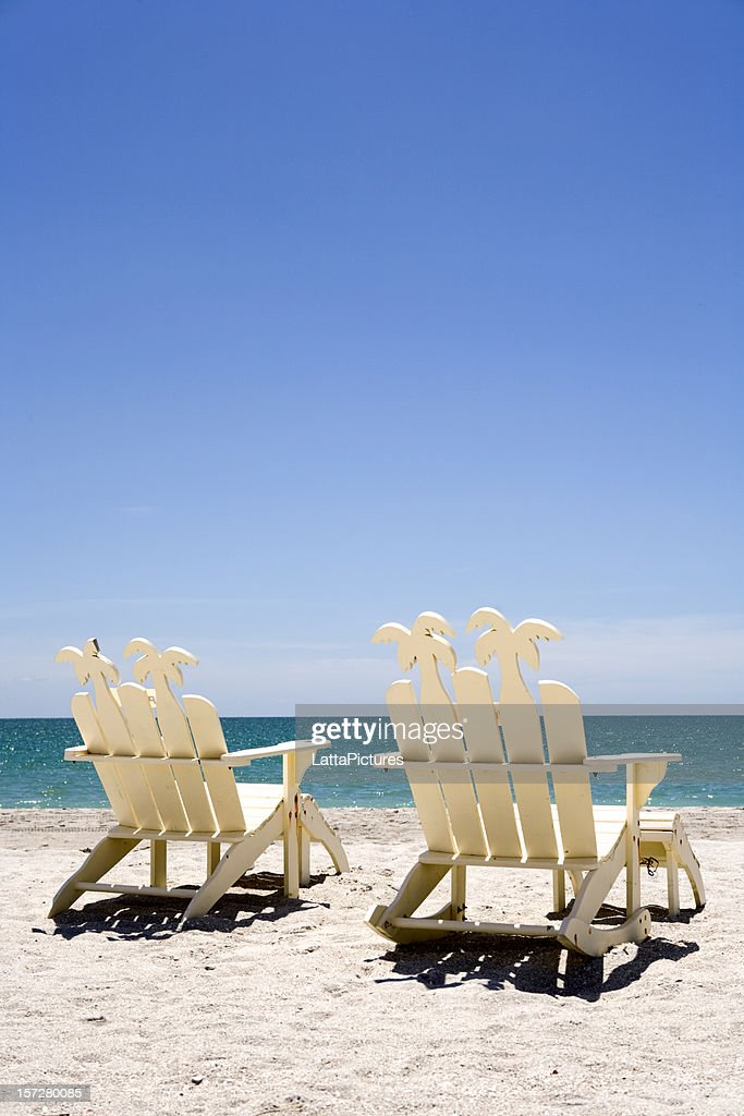 Two White Wooden Beach Chairs On Sand With Ocean Stock Photo
