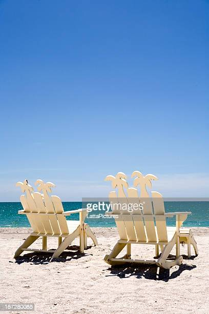 two white wooden beach chairs on sand with ocean - fort myers beach stock pictures, royalty-free photos & images