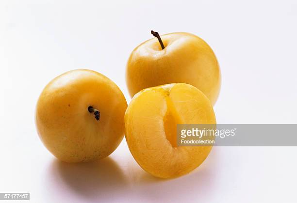 Two Whole Yellow Plums with One Half