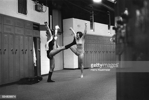 Two Wilde Lake High School students, both in leotards and with their arms raised, kick their legs out beside a bay of hallway lockers after a...