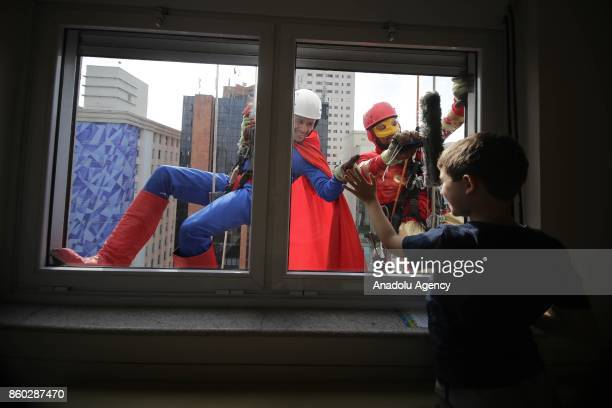 Two window washers dressed as Iron Man and Superman abseil the windows of a hospital specializing in cancer treatment as they greet a child patient...