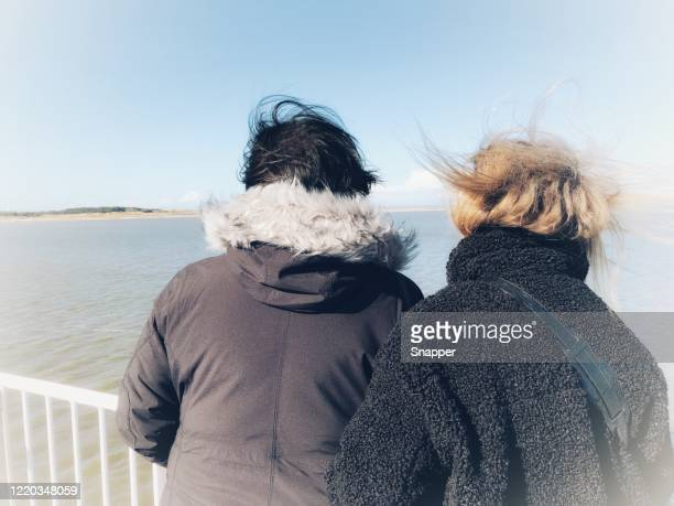 two windswept women standing on a boat looking at coastline, fanoe, jutland, denmark - female friendship stock pictures, royalty-free photos & images