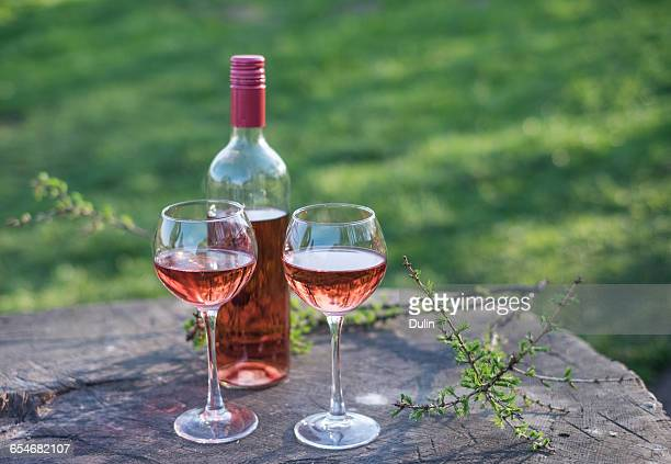 Two wine glasses and bottle of rose wine on wooden table