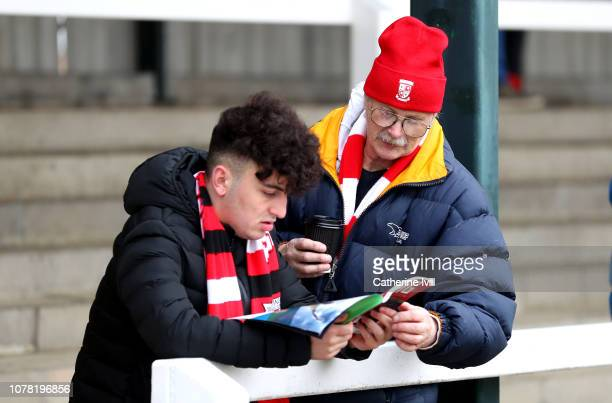 Two Woking fans read the match day programme prior to the FA Cup Third Round match between Woking and Watford at Kingfield Stadium on January 6 2019...