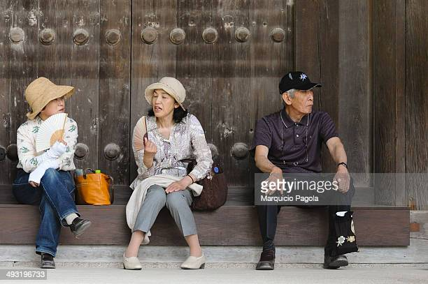 CONTENT] Two woman and an old man are taking a quick rest at Toshodaiji Temple Nara Nara Prefecture Japan The man is wearing black clothes and a...