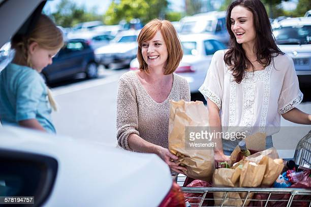 Two woman and little girl putting brown shopping bags in a car