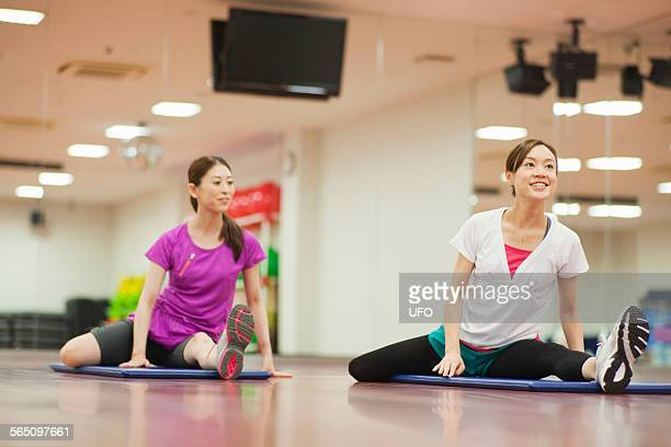 Two woman at gym warming up with leg stretches