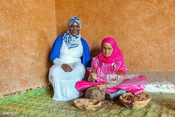 two woman at work for manufacturing argan oil in morocco - argan tree stock pictures, royalty-free photos & images