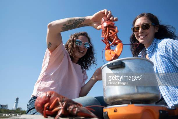 two woman boiling lobster outside near a lighthouse. - portland maine stock pictures, royalty-free photos & images