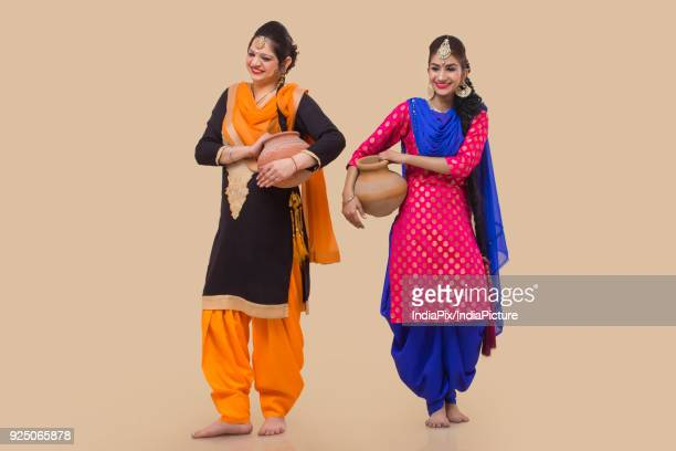 two woman carrying a earthen pot - salwar kameez stock pictures, royalty-free photos & images