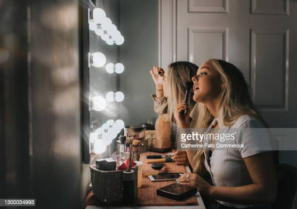 two woman concentrate as they apply make-up in an illuminated mirror - applying stock pictures, royalty-free photos & images