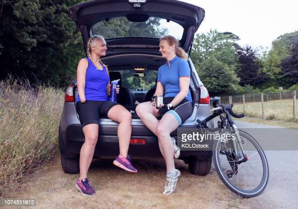 Two woman cyclist sitting down drinking