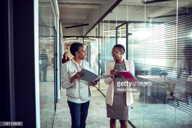 two woman discussing business on the way to the office - business meeting stock pictures, royalty-free photos & images