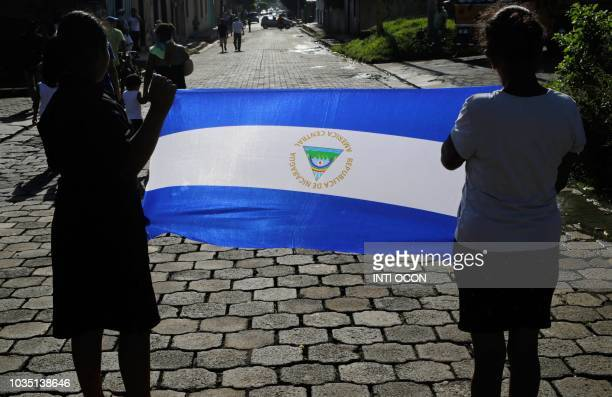 Two woman display a Nicaraguan national flag during the funeral procession of Bismark Martinez who died in hospital three months after being injured...