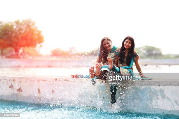 two woman doing fun in lake water - indian female feet stock pictures, royalty-free photos & images