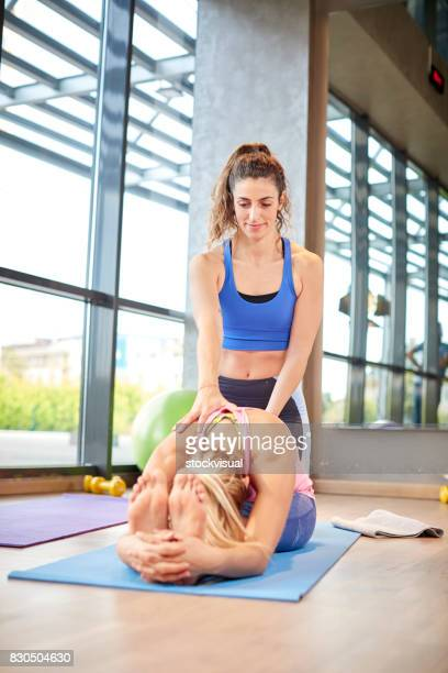 two woman doing streching in a class in a gym - woman straddling man stock pictures, royalty-free photos & images