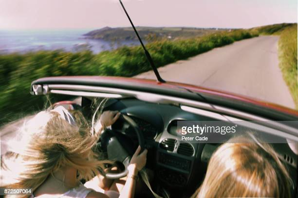 Two woman driving on coast road with roof down on car