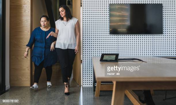 Two woman entering in meeting room.