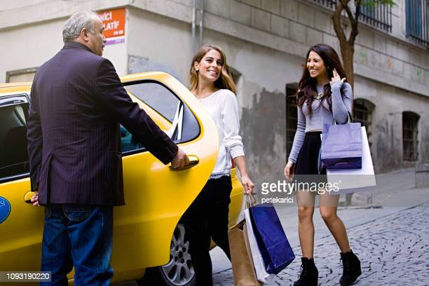 Two woman entering the taxi cab