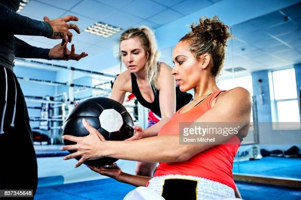 two woman exercising using medicine ball - circuit training stock photos and pictures