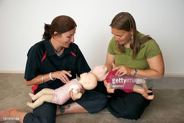 Two woman hold baby dummies so they can learn CPR