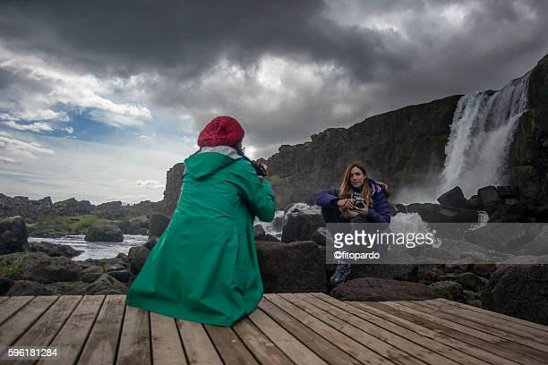 two woman in þingvellir national park with a water fall in background - thingvellir national park stock photos and pictures