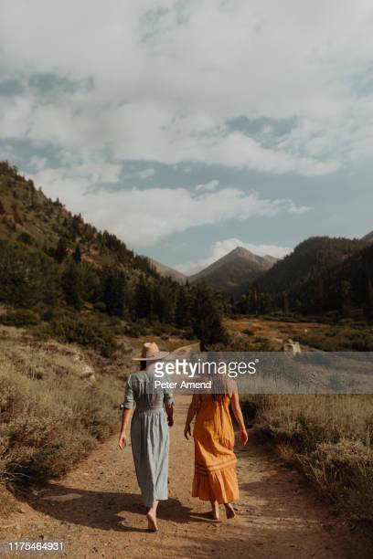 two woman in maxi dresses strolling on rural valley road, rear view, mineral king, california, usa - maxi dress stock pictures, royalty-free photos & images