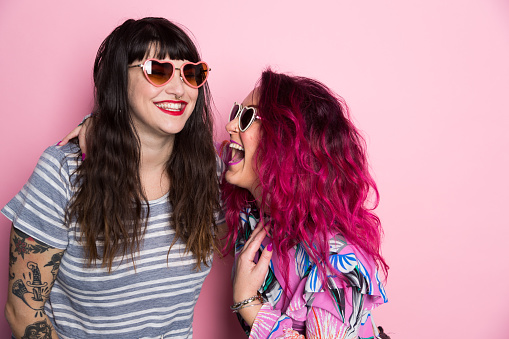 Two woman laughing against a pink back ground - gettyimageskorea