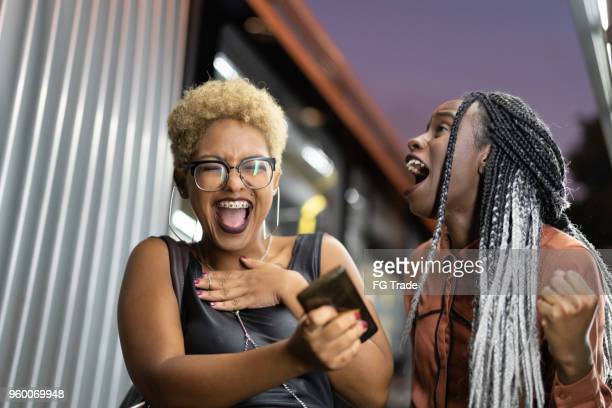two woman laughing with funny media on mobile - downtown comedy duo stock pictures, royalty-free photos & images