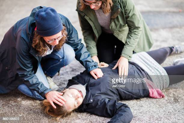 Two woman looking after unconscious woman