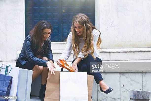 Two woman  looking excited at her orange shoes